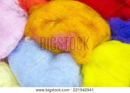 An overhead photo colorful natural sheep wool for felting. Dry merino bright colorful wool. Blue, orange, white and yellow dried yarn for the creative craft fashion work