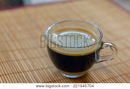 espresso coffee with golden fine-bubbled crema seen from above in a crystal clear cup on bamboo plate holder. Stock photo