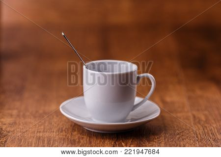 one white coffe Cup with spoon on white saucer on dark brown wooden background. morning concept