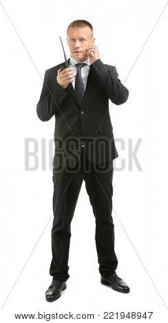 Male security guard using portable radio transmitter on white background