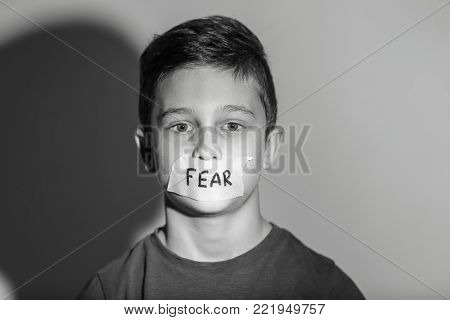 Sad little boy with taped mouth and word