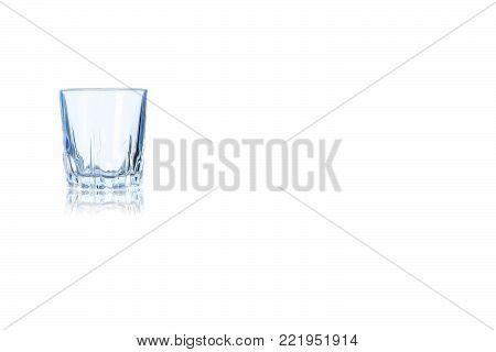 An empty shot of vodka or tequila toned in blue colorisolated on a white background. Place for your text.