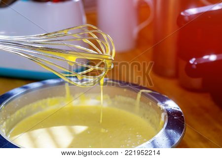 Mixing egg, flour and sugar cream in bowl with motor mixer. Kneaded dough for baking a cake