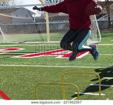 A track and field athlete jumping toward the camera over yellow mini hurdle on a green turf athletic field on a sunny afternoon.