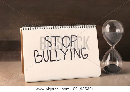 "Notebook with text ""Stop bullying"" and hourglass on table poster"