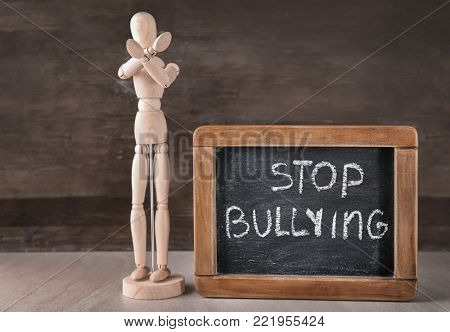 Wooden figure and chalkboard with text