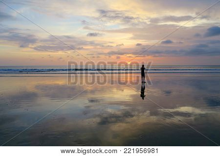 Lonely photographer making photo of sunset with reflection at Kuta beach, Bali, Indonesia