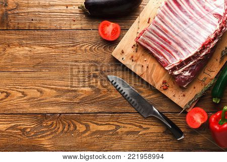 Raw rack of lamb. Fresh meat, vegetables and knife on wooden board on rustic table. Organic ingredients for restaurant meals, copy space, top view