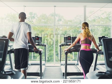 Happy couple run on treadmills. Man and tired woman cardio workout in fitness club. Healthy lifestyle, training in gym. Flare effect, copy space