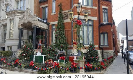Christmas Holiday Decorations Red Bows, Rocking Horses and a Christmas Tree adorning the exterior of a house at a street corner with a gaslight