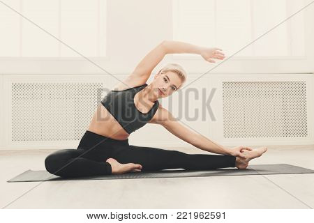 Fitness woman warmup stretching training, sitting on mat indoors. Young slim girl makes aerobics exercise, copy space