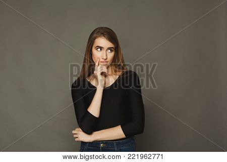 Pensive thoughtful woman standing on brown background and thinking. Concentrated girl posing and making decision, copy space