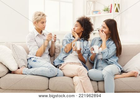 Three young female friends with coffee cups talking in living room at home, chatting about their life and relations, surprised with news, gossip and slumber party concept, copy space