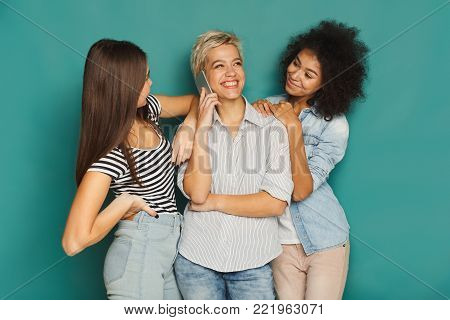 Girls overhearing her friend mobile phone talk at home. Young women having fun, making group conversation, copy space