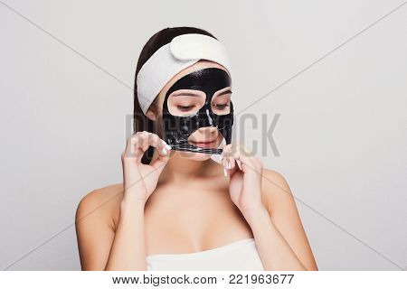 Skin care. Portrait of young girl peeling off black mask from her face. Purifying spa treatment, white studio background, copy space