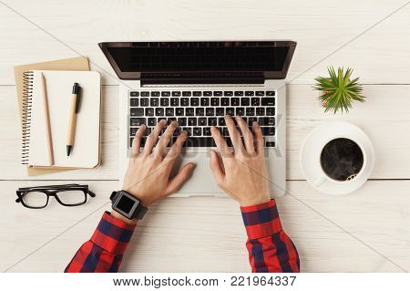 Man's hands on laptop keyboard, blank screen for advertisement. Top view of human hands, laptop keyboard, coffee, notebook on white wooden table background. Education, business, technology concept