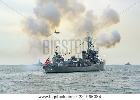 Pattaya, Thailand - November 20, 2017, Navy warship gunning salute on sea whle warplane above the ship on the 50th anniversary ASEAN international fleet review 2017 in Pattaya, Thailand