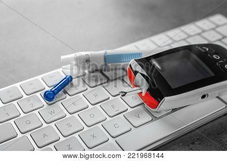Digital glucometer and lancet pen on computer keyboard. Diabetes management
