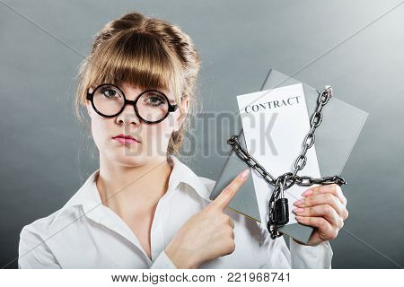 Business concept, limited by contract. Woman holding in hands paper document chained with padlock