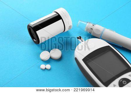 Digital glucometer, lancet pen and medicaments on color background. Diabetes management