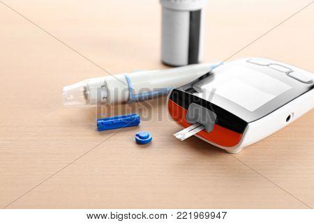 Digital glucometer and lancet pen on table. Diabetes management