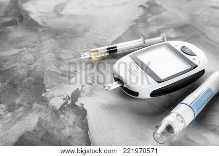 Digital glucometer and lancet pen on grey background. Diabetes management