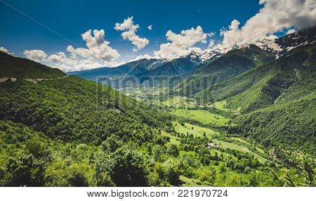 Panoramic summer landscape with green hill and mountain snow capped peak against blue cloudy sky. Svanetia region, Georgia. Main Caucasian ridge. Nature background. Holiday, hiking, travel, recreation