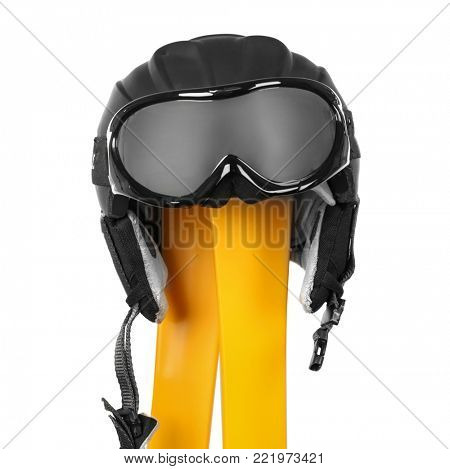 Yellow skis with goggles and helmet on white background. Winter vacation concept