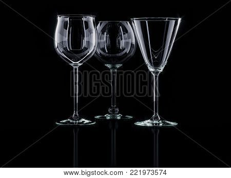 3D rendering. Wine glasses on black. Three glasses of different shapes on a deep black background. Fine glassware. Transparent glass of noble wine.