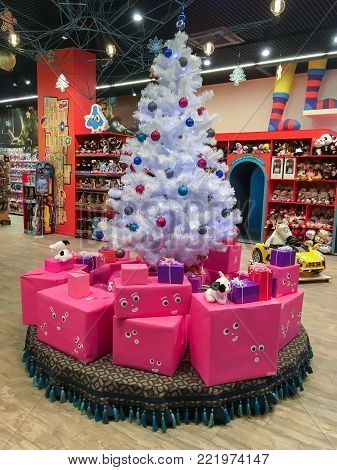 LVIV, UKRAINE - DECEMBER 22: White Christmas tree and gifts under it in the children's store in the shopping and entertainment center