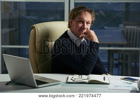 Portrait of smiling entrepreneur with dishevelled hair sitting at his table in office
