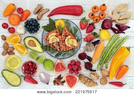 Healthy diet food to promote heart health concept with superfoods of salmon, fruit, vegetables, nuts, spice and herbs providing high levels of omega 3 fatty acids, anthocyanins and antioxidants.