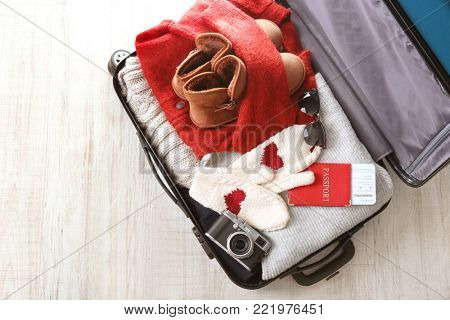 Open suitcase with warm clothes, photo camera and documents on wooden floor. Winter vacation concept