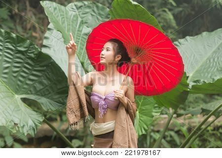 Beautiful Thai girl in Thai costume in a Sunny Park with a red umbrella,Asian woman wearing traditional Thai culture at the forest in countryside.