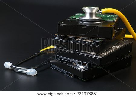 Internal SATA type hard disk drive and stethoscope with copy space on black background for protect data, repair, fixed, service and recovery concept. Computer hardware hard disk concept. poster