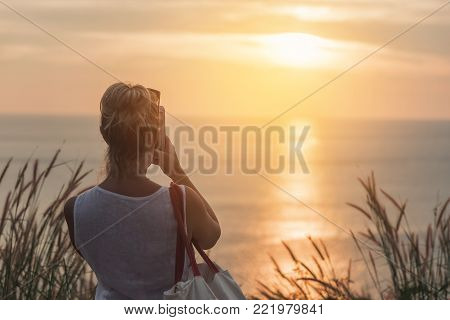 woman taking photos of sunset with mobile phone.view on Koh Phuket island,Thailand