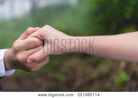 Newly-married couple holding hands in the garden