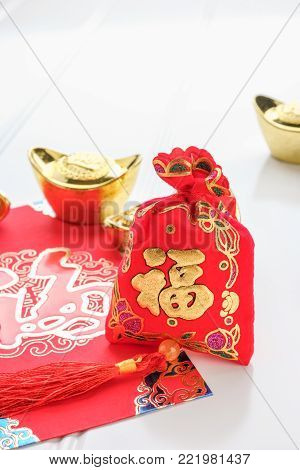 Chinese New year,ang pow red felt fabric bag with gold ingots and oranges and flower on white wood table top,Chinese Language mean Happiness and on ingot mean wealthy poster
