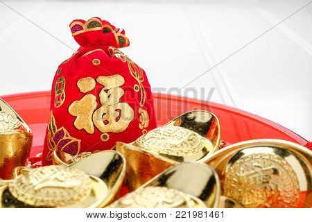 Chinese New year ang pow red felt fabric bag with gold ingots in red tray on white wood table top,Chinese Language on bag mean Happiness and on ingot mean wealthy