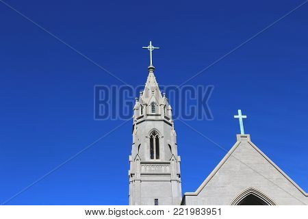 Catholic church with crosses against blue sky copy space in Culver City, California.