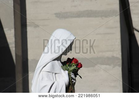 statue of Mary mother of God holding roses near St Augustine's Catholic Church in Culver City, California.