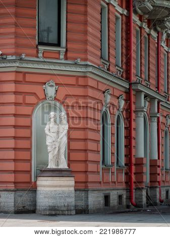 The facade of the building with marble statues in a niche on Shpalernaya Street in St. Petersburg in April