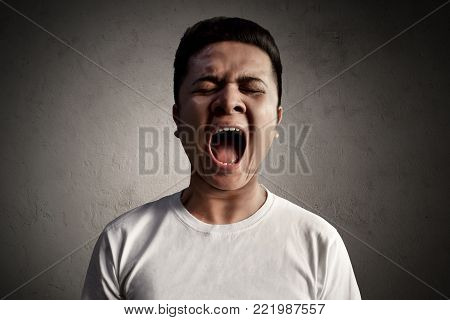 Asian man angry and screaming loud expression