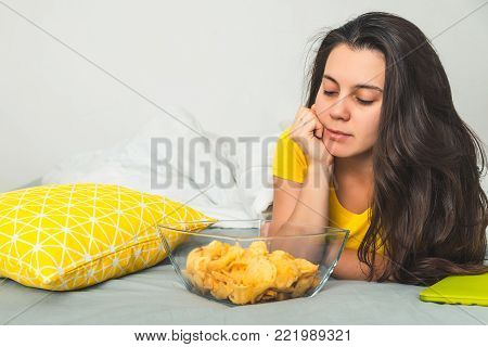woman lie on the bad watch movie and eat snaks front view