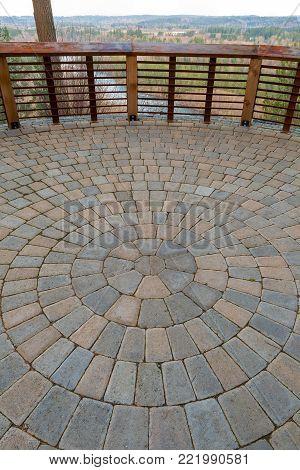 Garden Backyard circular brick stone pavers hardscape patio with wood railings stone wall view deck