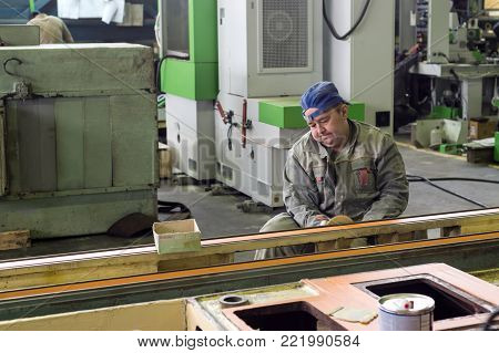 Lipetsk, Russia - June 15, 2017: The worker polishes the primer layer. Work on the preparation of the machine bed for subsequent painting.