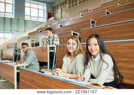 Multi-ethnic  group of people sitting at separate tables in lecture hall of modern college, focus on two beautiful girls looking at camera and smiling