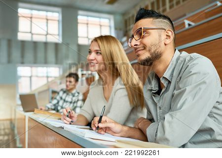 Multi-ethnic group of students sitting at desk in lecture hall of modern college and smiling happily, focus on young Middle-Eastern man wearing glasses, copy space