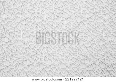 The white background of delicate lace. Delicate texture fabric close. Cloth weave decorative.  Textile weave patterned.
