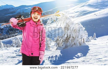 Girl skier standing with skis in the picturesque mountains between the Christmas trees